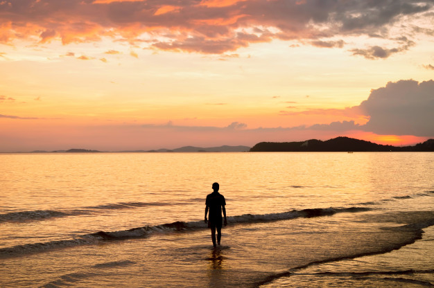 silhouette-of-lonely-man-walking-in-to-the-sea-at-sunset_42299-73