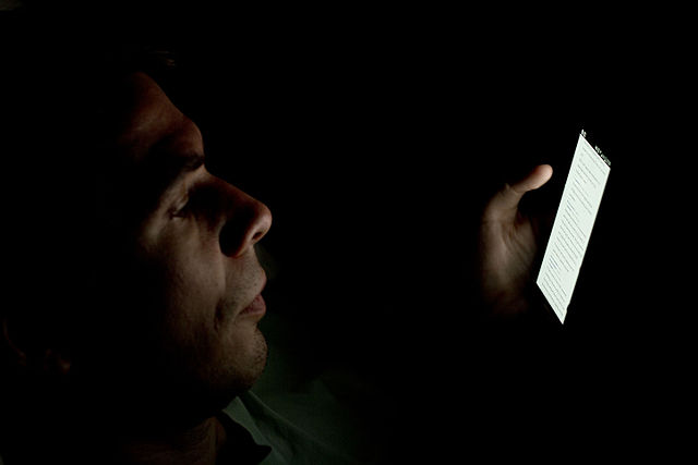 640px-Person_looking_at_smartphone_in_the_dark_2