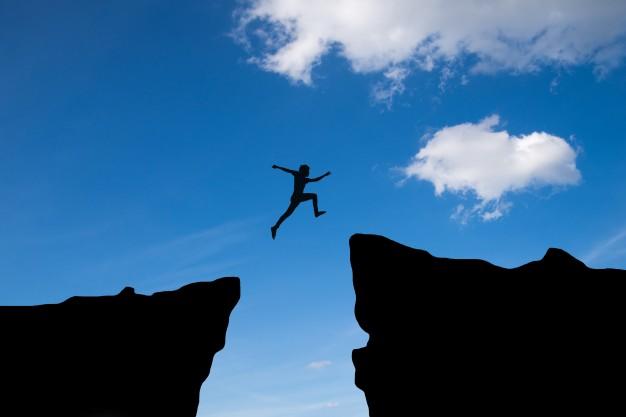 man-jump-through-gap-hill-man-jumping-cliff-blue-sky-business-concept-idea_1323-185